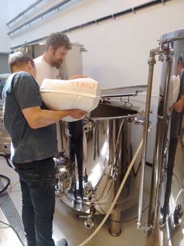 Adding the grains to the large mash tun.